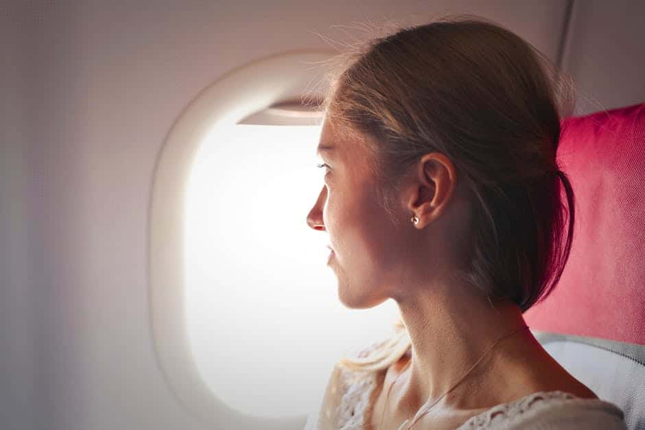 Selective Focus Photo of Woman Sitting on Chair Looking Outside Window on Plane